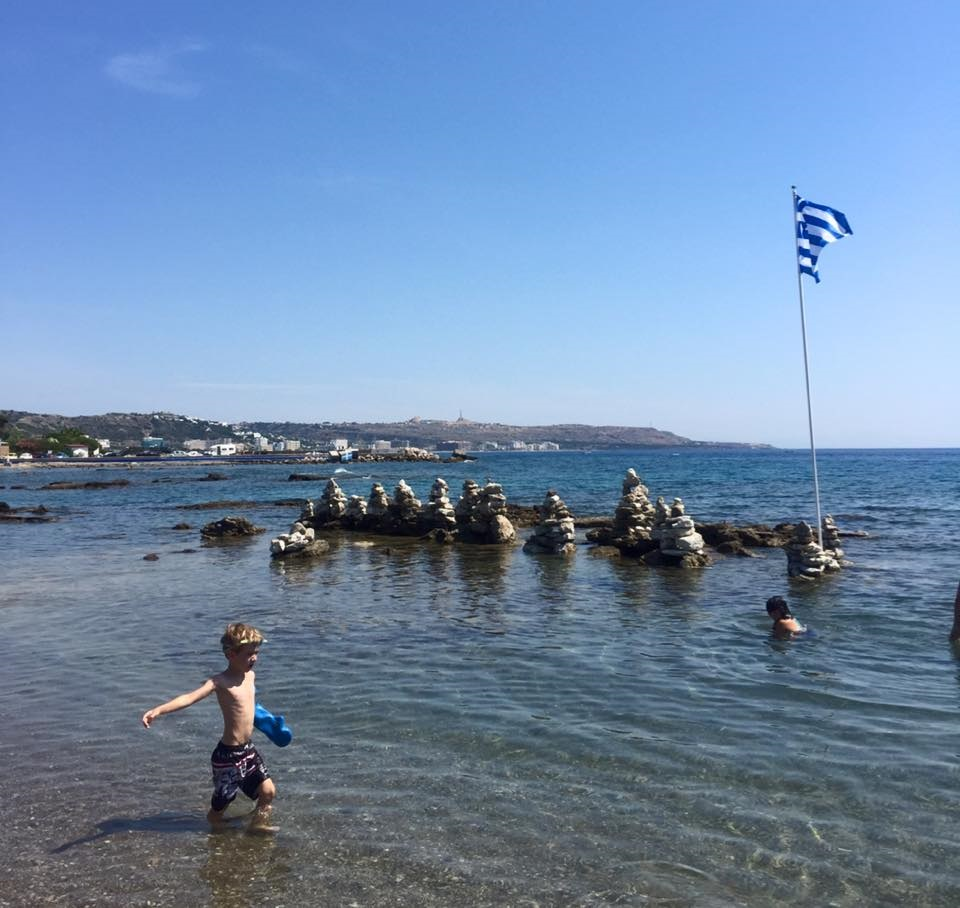 a child wading in the sea wearing a bloccs arm cast protector