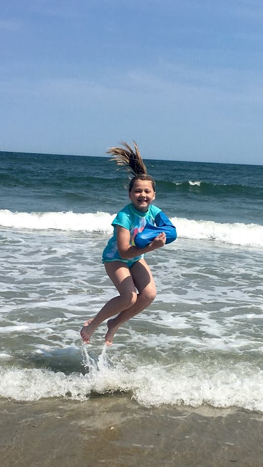 a girl jumping in the sea wearing a bloccs arm cast protector