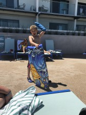 a child on the beach holding a bodyboard and cheering, an arm raised wearing a bloccs cast protector