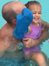a father holding his child in the pool who is wearing a bloccs cast protector